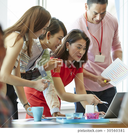 A group of four people is working at office 30560381