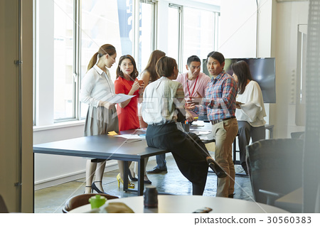 a group of people is discussing at office 30560383