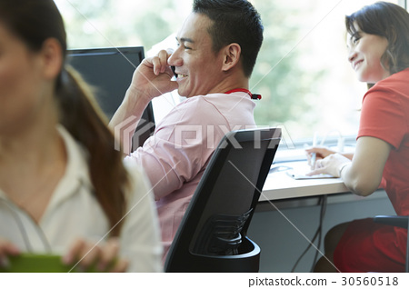 A woman is smiling and looking at a man talking on phone 30560518