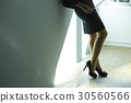 Low parts of a businesswoman standing in office. 30560566