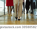 Legs of people standing in the office. 30560582