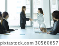 Two businesswomen are shaking hands and colleagues are watching. 30560657