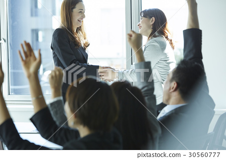 two women smiling and shaking hand with a cheer from others 30560777