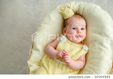 Newborn baby girl lying in a basket with crown and 30564989