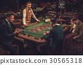Upper class friends gambling in a casino 30565318