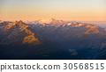 Warm light at sunrise on mountain peaks 30568515