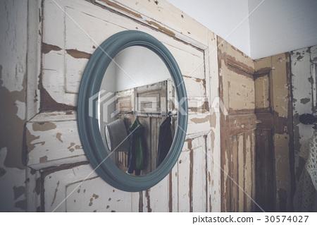 Round mirror hanging on a grunge wooden wall 30574027