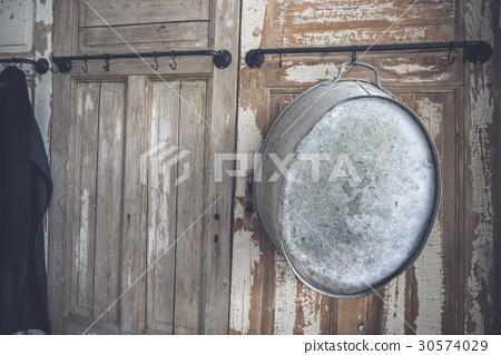 Old metal tub hanging on a hook 30574029