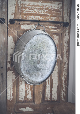 Old stylish iron tub hanging on a wooden wall 30574030