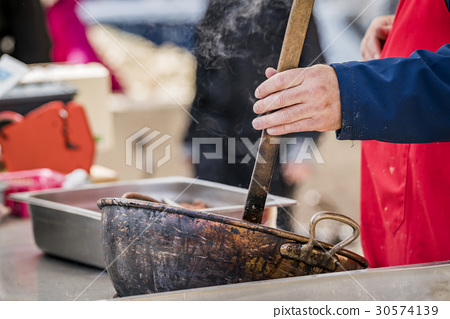 Outdoor kitchen with a man stirring in a hot pot 30574139