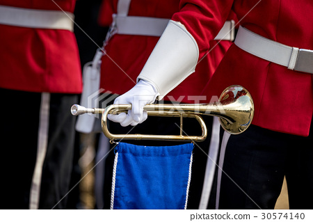 Soldier in red uniform holding a golden trumpet 30574140