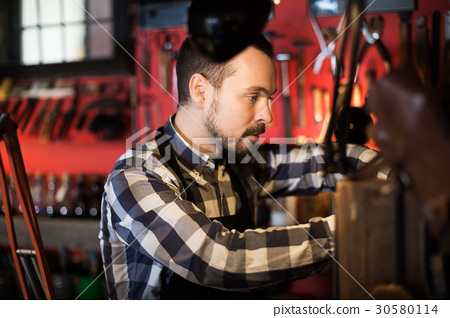 Worker processing leather for belt 30580114