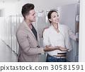satisfied couple choosing new refrigerator in hypermarket 30581591