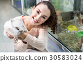 Portrait of young smiling woman holding fluffy animal 30583024