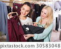 Happy young positive female friends choosing trousers 30583048