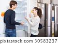 family couple choosing new refrigerator in hypermarket 30583237