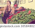Seller holding fresh paprika in hands in supermarket 30584802