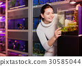 Girl with interest looking at small fry fish in aquarium with seaweed in aquarium shop 30585044