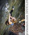 Woman rock climbing with carbines and rope 30593120