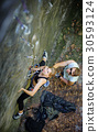Woman rock climbing with carbines and rope 30593124