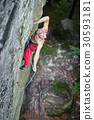 Rock climber climbs on cliff wall with rope 30593181