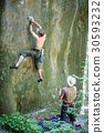 Rock climber climbs on cliff wall with rope 30593232