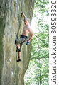 Rock climber climbs on cliff wall with rope 30593326