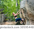 young woman climbing on large boulders outdoor 30595448