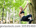 young woman climbing on large boulders outdoor 30595460