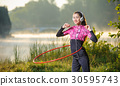 Girl doing hula hoop outdoors near the lake 30595743