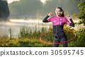 Girl doing hula hoop outdoors near the lake 30595745