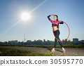 girl standing with hula hoop outdoors 30595770