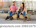 Couple on rollerblades sitting. 30601679