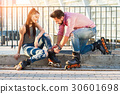 Woman and man wearing rollerblades. 30601698