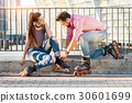 Young couple is wearing rollerblades. 30601699