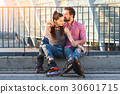 Couple on rollerblades sitting. 30601715
