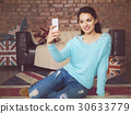 Young beautiful woman sitting with smart phone 30633779