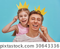 Dad and child are holding paper crown 30643336