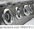 Row of washing machines in a public laundromat. 30647411