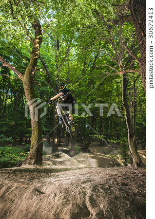 Man bikes in the green forest. 30672413
