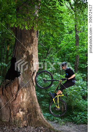Man bikes in the green forest. 30672417