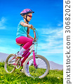 Child traveling bicycle in rainbow goggles and 30682026