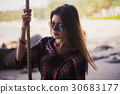 Cute girl posing on a beach. She holds a rope and 30683177
