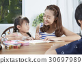 mother is teaching her daughter with pencil and notebook. 30697989