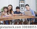 A portrait of young family doing work together at the table 30698055