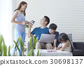 mom is giving water for dad while kids are drawing and watching. 30698137