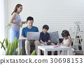 Dad is working on the laptop next to mom while the kids are studying. 30698153