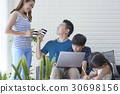mother is giving water to father while kids are studying. 30698156