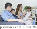 The happy family is sitting on the sofa at home. 30698199