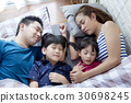 Cute family is sleeping together in bed. 30698245